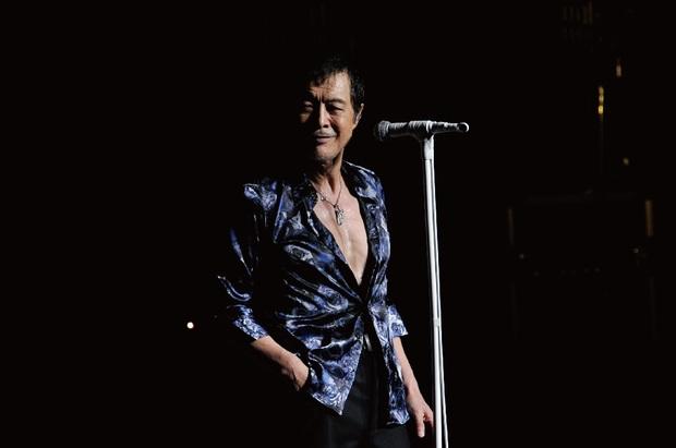 青いシャツを着てポケットに手を入れている矢沢永吉の画像