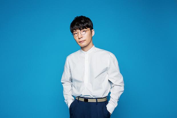 青い背景で白いシャツの星野源